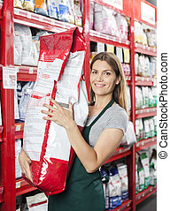 Saleswoman Carrying Large Food Package In Pet Store -...