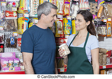Saleswoman Holding Pet Food While Looking At Customer -...