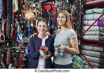Smiling Mother And Daughter Holding Toys For Pet - Portrait...