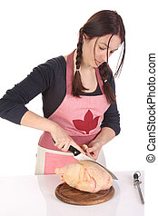 beautiful housewife cutting chicken on white background