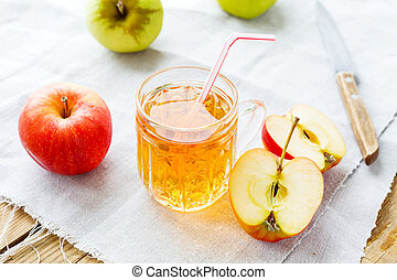 Rustic background with apples and apple juice in glass on...
