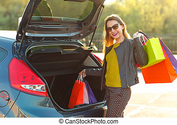 Woman putting her shopping bags into the car trunk - Smiling...