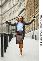 Delighted business woman jumping for joy while talking on...