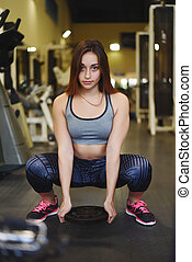 Athlete young woman doing exercise at gym. - Attractive...