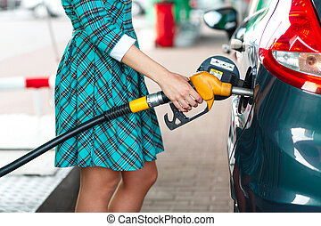 Woman fills petrol into the car at a gas station - Woman...