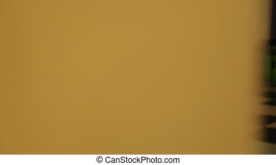 The woman is showed from the beige wall angle working with...