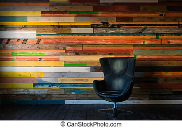 Modern egg chair on a colorful wooden wall