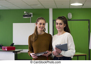 Firneds at School - Two teenage girls standing together in a...