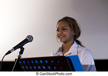 Making a Speech - Female student making a speech. She is...