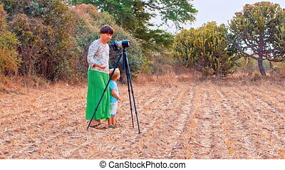 Mother photographer taking pictures - Young woman takes...