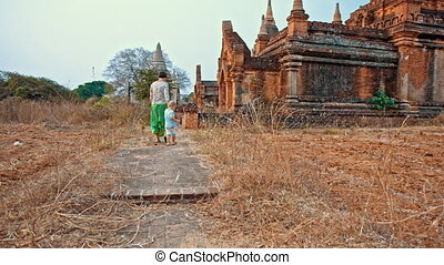 reach the temple - young woman walks with toddler son to...