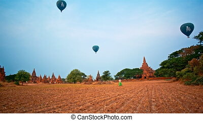 Balloons over Temples in Bagan, Mya - Young woman takes...