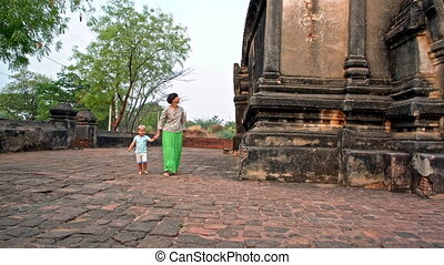 walk along the temple walls - young woman walks with toddler...