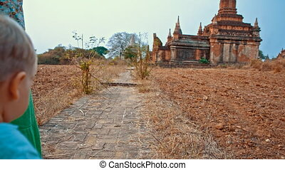 walk to the temple - young woman walks with toddler son on...