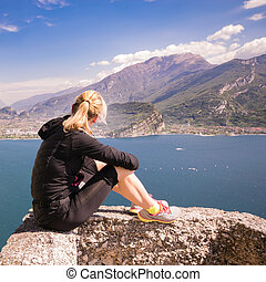 Sporty woman admire the panorama from the Ponale trail in...