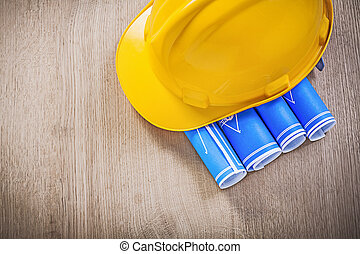 Wooden board with blue blueprints hard hat construction concept