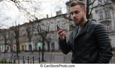 Handsome man talking on his phone in the street.