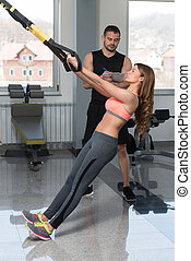 Gym Coach Helping Woman On Trx Fitness Straps - Personal...