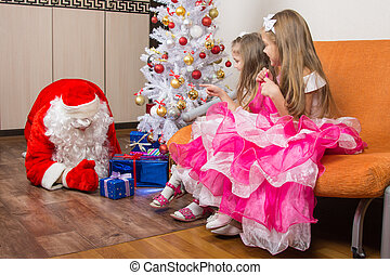 Two girls saw that Santa Claus puts presents under the...