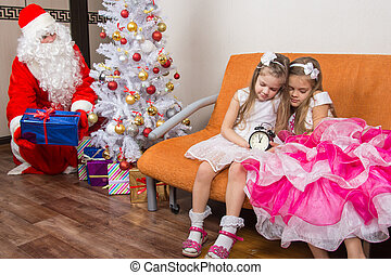 The sisters fell asleep while waiting for Santa Claus, who quietly put presents under the Christmas tree