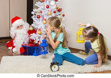 Two girls with flashlights to see Santa Claus who was trying to discreetly put the presents under the Christmas tree