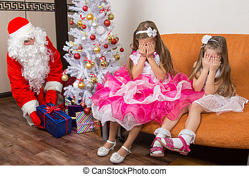 Two girls closed eyes with his hands until Santa Claus put...
