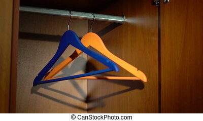 Swinging hangers in a wardrobe - Swinging blue and orange...