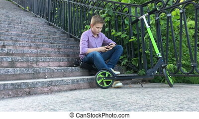 Boy sitting on the stairs in a park and writes on the phone...