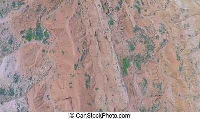 Aerial video of red rocks with scarce vegetation and dried...