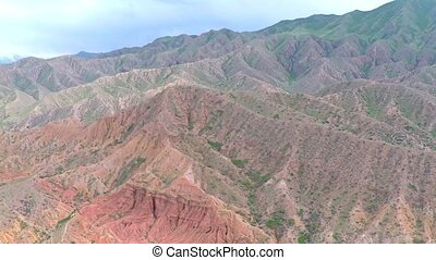Aerial video of red rocks with scarce vegetation and distant...
