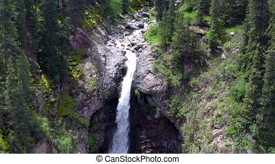 Aerial video of high waterfall in mountain spruce forest....