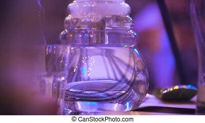 The flask hookah bubble. Night club or bar, people smoke...
