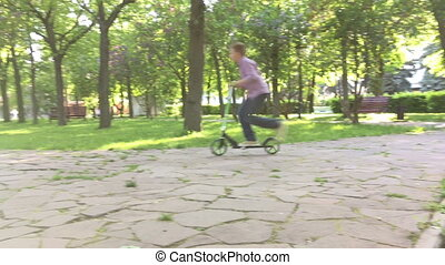 Boy with scooter having fun in the park 4K