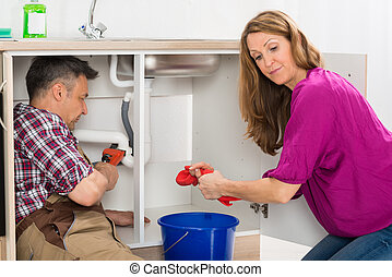 Plumber Repairing Pipe Under Sink - Male Plumber Repairing...