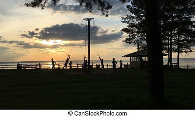 Children at sunset ride on a swing HD