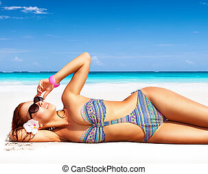 Beautiful woman on the beach, lying down on clean white...