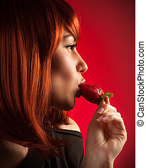 Seductive woman eating strawberry