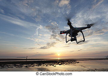 Drone flying against a sunse - Remote controlled drone...