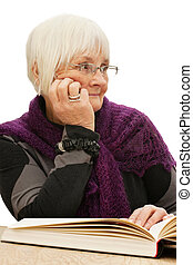 Relaxed old woman looking away while reading a book -...