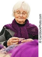 Portrait of elderly woman knitting against white - Portrait...
