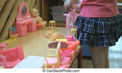 Little girl playing children's furniture at table