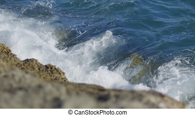 Shot over small waves around rocks Indian ocean