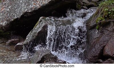 Super slow motion video of small mountain river waterfall -...