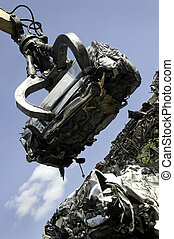 Lifted scrap car - A scrap car being lifted by grab crane on...
