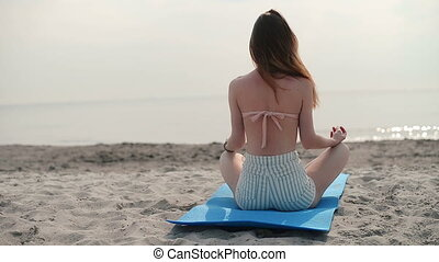 Woman meditating on beach in lotus position - Woman...