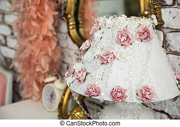Close-up of a lampshade with pink roses and beads on the...