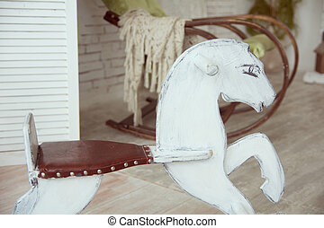 Old wooden rocking horse on a background of an old rocking...
