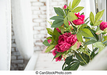 Red flowers on the window sill on the brick wall background