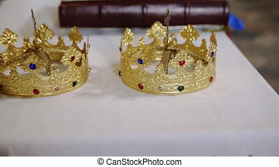Two golden crowns and bible on white table prepared for...