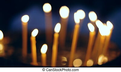 Burning candles in sconces on black blue background, close up